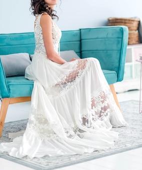 Panna młoda w białej sukni ślubnej bohemy siedzi na niebieskim krześle. zdjęcie pionowe