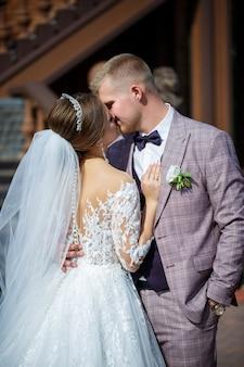 Panna młoda w białej sukni ślubnej i pan młody w garniturze na tle ceglanego budynku z dużymi schodami