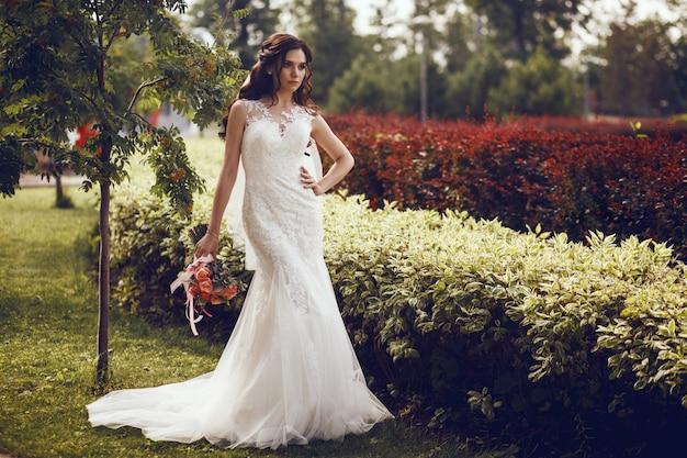 Panna młoda w białej sukni ślubnej stoi na tle sztucznego wodospadu w parku miejskim