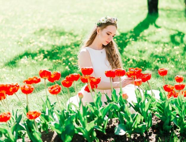 Panna młoda w białej sukni ślubnej trzyma bukiet w zielonym parku. letni ślub w słoneczny dzień.