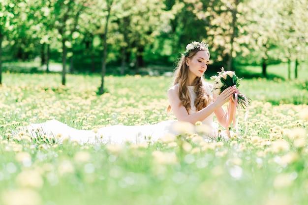 Panna młoda w białej sukni ślubnej trzyma bukiet w zielonym parku