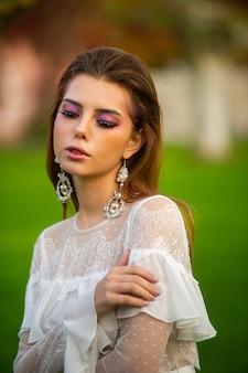 Panna młoda w białej sukni ślubnej w parku w austriackim miasteczku z dużymi drzewami o zachodzie słońca.