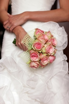 Panna młoda w białej sukni ślubnej z bukietem róż