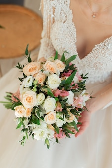 Panna młoda w białej sukni trzyma bukiet ślubny. bukiet z bliska. poranek panny młodej