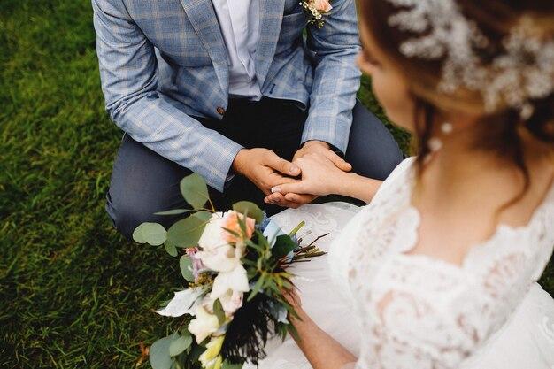 Panna młoda w białej sukni trzyma bukiet ślubny. pan młody trzyma ją za rękę.