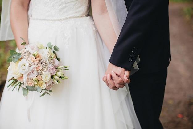 Panna młoda w białej sukni trzyma bukiet ślubny. pan młody trzyma rękę panny młodej.