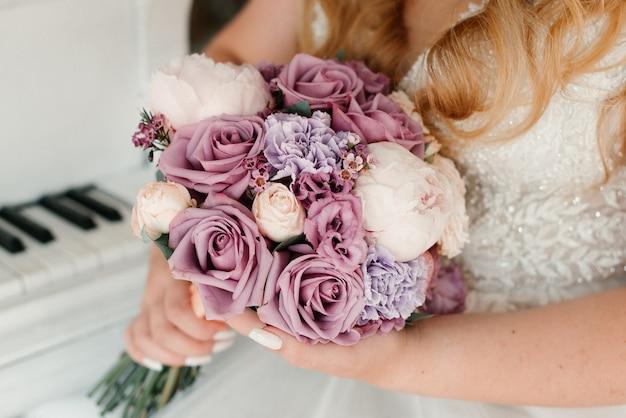 Panna młoda w białej sukni trzyma bukiet ślubny. szczegóły ślubu
