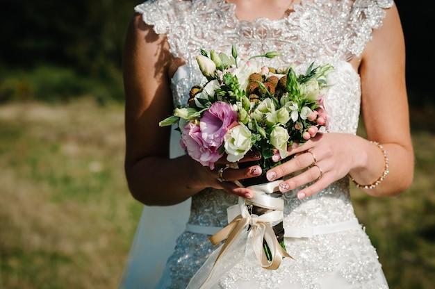 Panna młoda w białej sukni trzyma bukiet ślubny z różowych kwiatów