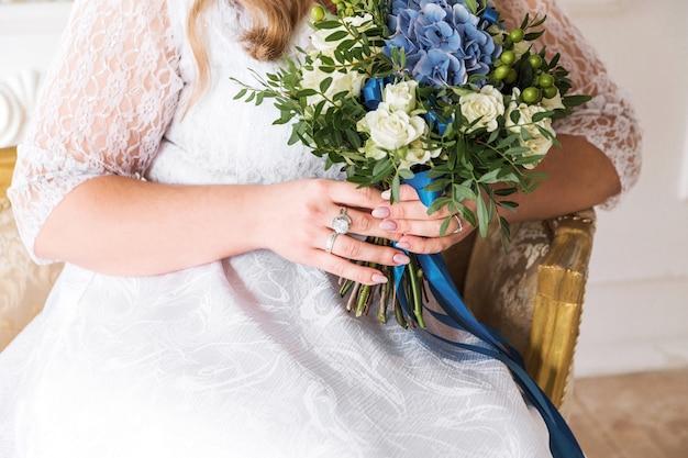 Panna młoda w białej sukni trzyma bukiet w dłoniach