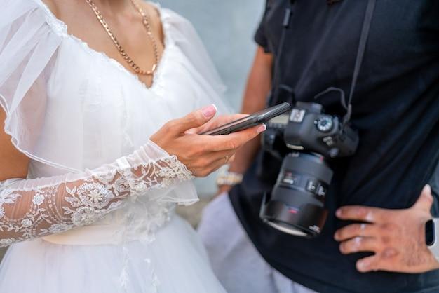 Panna młoda w białej sukni trzyma w dłoni smartfon.