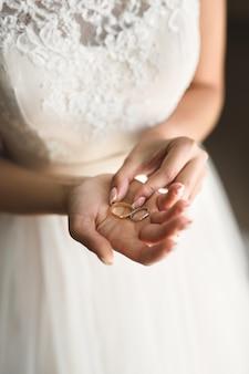 Panna młoda w białej sukni trzyma w rękach złote obrączki ślubne
