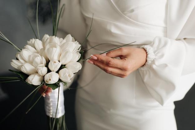 Panna młoda w białej sukni z bukietem ślubnym w rękach szczegóły ślubne