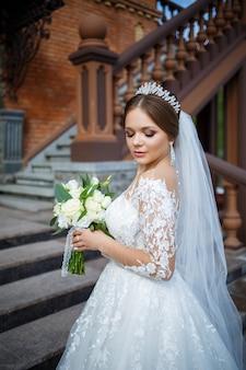 Panna młoda w białej sukni z bukietem w dłoniach i koroną na głowie
