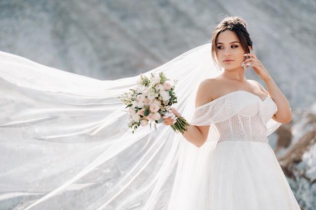Panna młoda w białej sukni z bukietem w ręce na górze