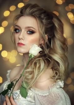 Panna młoda w białej sukni z lokami na głowie trzyma różę przy twarzy na tle żółtego bokeh.