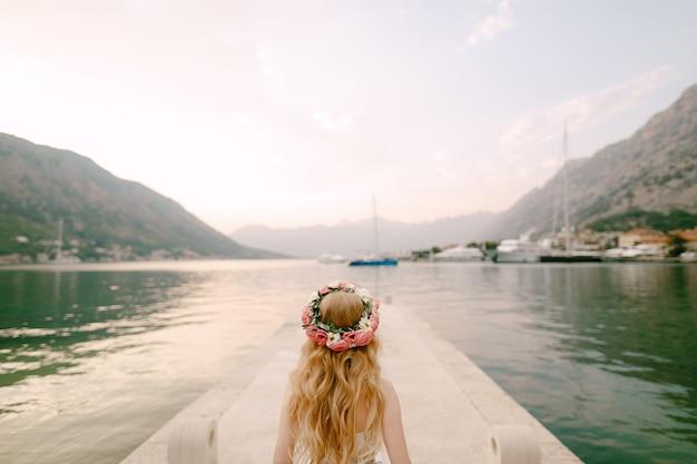 Panna młoda w delikatnym wieńcu róż stoi na molo niedaleko kotoru w zatoce kotorskiej, widok z tyłu. wysokiej jakości zdjęcie