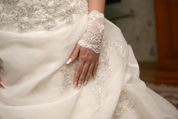 Panna młoda w dłoni leżącej na sukni ślubnej