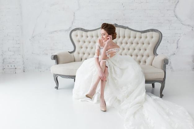 Panna młoda w długiej sukni siedzi na kanapie pomieszczeniu w biały studio wnętrz, jak w domu.