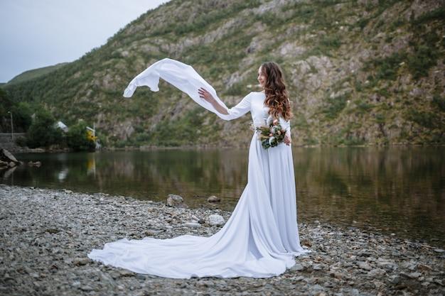 Panna młoda w długiej sukni ślubnej stojącej nad brzegiem jeziora, z trzepoczącymi rękawami sukni