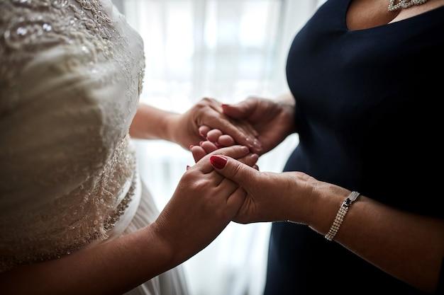 Panna młoda w dniu ślubu, trzymając się za ręce matki