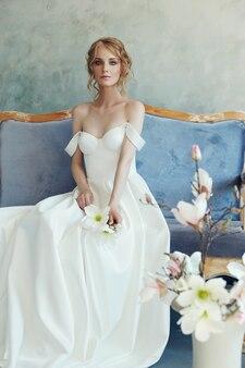 Panna młoda w eleganckiej długiej sukni leżącej na kanapie.