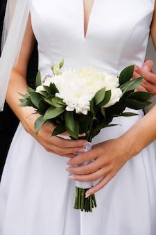 Panna młoda w eleganckiej sukni ślubnej trzyma piękny bukiet białych róż i chryzantem i zielonych liści. objąć nowożeńców, ręce narzeczonej z bliska, na zewnątrz.