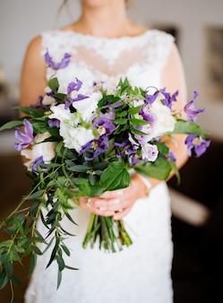 Panna młoda w koronkowej sukience trzyma niezwykły bukiet z fioletowymi różami powojników i zielonymi gałązkami