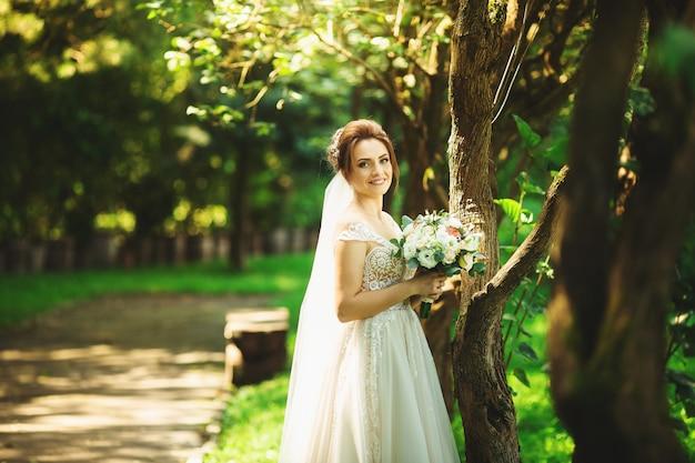 Panna młoda w mody ślubnej sukni na naturalnym tle. piękny kobieta portret w parku
