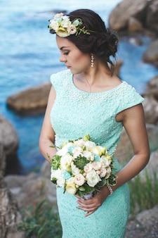 Panna młoda w naturze w górach blisko wody. kolor sukienki tiffany. panna młoda pozuje z bukietem.