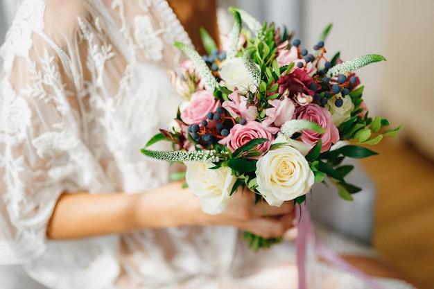 Panna młoda w peniuar z białej koronki trzyma w dłoniach bukiet ślubny w pokoju hotelowym