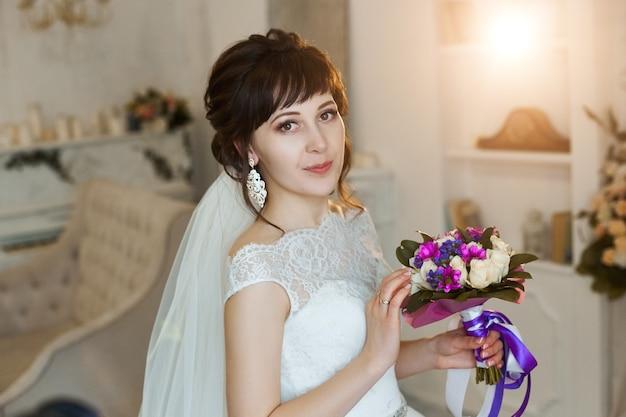 Panna młoda w pięknej białej sukni przygotowuje się do ceremonii ślubnej. poranek panny młodej