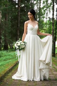 Panna młoda w pięknej białej sukni z bukietem kwiatów w dłoniach czeka na ceremonię ślubną.