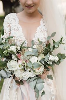 Panna młoda w pięknej sukience trzyma bukiet ślubny z eukaliptusa i białych róż