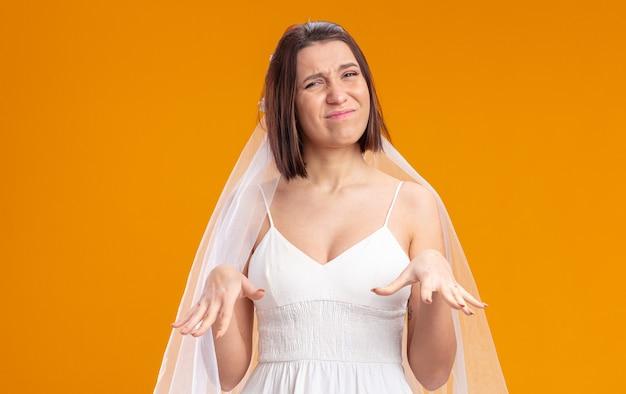 Panna młoda w pięknej sukni ślubnej patrząca z przodu zdezorientowana i niezadowolona, wykonując gest uspokojenia rękami stojąc nad pomarańczową ścianą