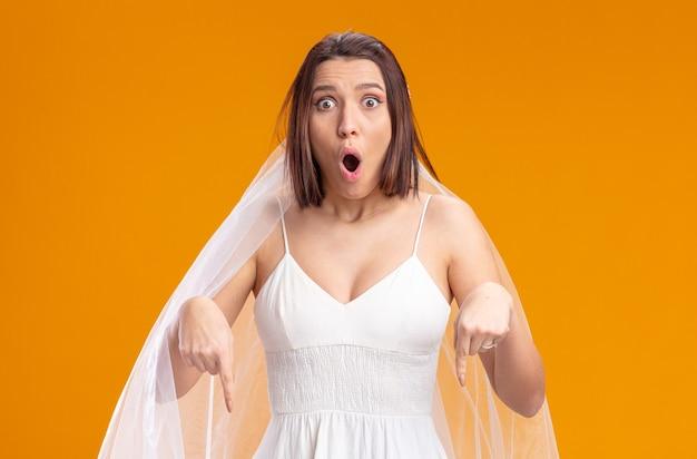 Panna młoda w pięknej sukni ślubnej zdumiona i zdziwiona, wskazując palcem wskazującym w dół
