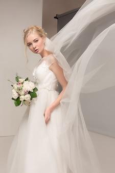 Panna młoda w pięknej sukni stojącej w pomieszczeniu w białym wnętrzu studio jak w domu.