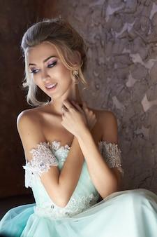 Panna młoda w pięknej turkusowej sukience w oczekiwaniu na ślub. blondynka w koronkowej sukience w kolorze morskiej zieleni. szczęśliwa panna młoda, emocje, radość na twarzy. piękny makijaż manicure i fryzura dla kobiet
