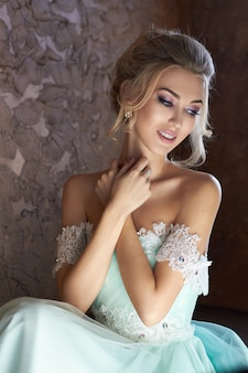 Panna młoda w pięknej turkusowej sukni w oczekiwaniu na ślub. blondynka w koronkowej sukience w kolorze morskiej zieleni. szczęśliwa panna młoda, emocje, radość na jego twarzy. piękny makijaż kobiety do manicure i fryzury