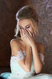 Panna młoda w pięknej turkusowej sukni w oczekiwaniu na ślub. blondynka w koronkowej sukience w kolorze morskiej zieleni. szczęśliwa panna młoda, emocje, radość na jego twarzy. piękny makijaż, manicure i fryzura kobiet