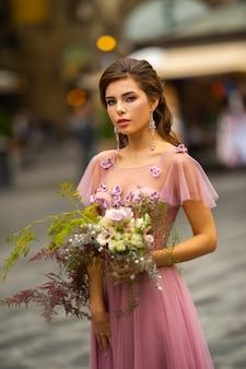 Panna młoda w różowej sukience z bukietem stoi w centrum starego miasta we florencji we włoszech.