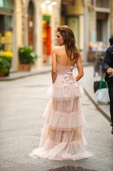 Panna młoda w różowej sukni ślubnej spaceruje po florencji we włoszech.