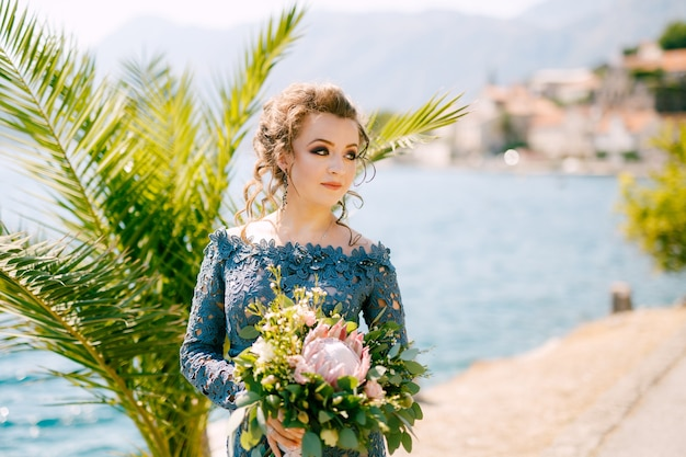 Panna młoda w stylowej szarej sukience stoi z bukietami ślubnymi na molo w pobliżu starego miasta perast