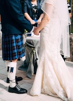 Panna młoda w sukni ślubnej i pan młody w szkockiej narodowej sukni stoją trzymając się za ręce