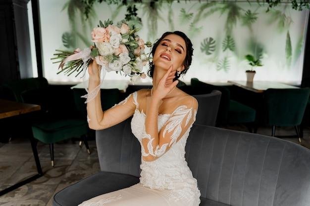 Panna młoda w sukni ślubnej na krześle moda w kawiarni.