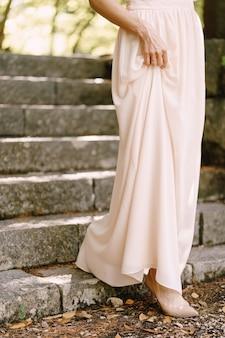 Panna młoda w sukni ślubnej schodzi z bliska po kamiennych schodach