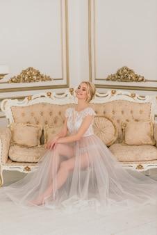 Panna młoda w sukni ślubnej siedzi w pokoju