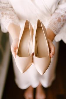 Panna młoda w sukni ślubnej trzyma w dłoniach buty na wysokim obcasie