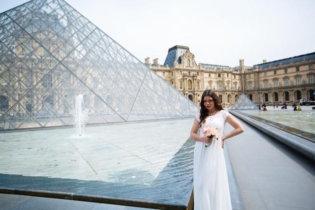 Panna młoda w sukni ślubnej w paryżu w luwrze