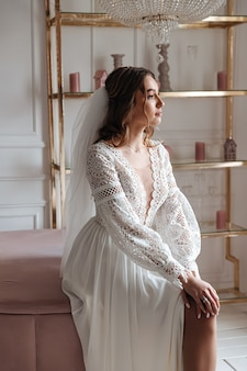 Panna młoda w sukni ślubnej w stylu boho z welonem pozuje siedząc w przytulnym pokoju.