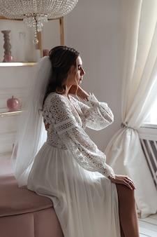 Panna Młoda W Sukni ślubnej W Stylu Boho Z Welonem Pozuje Siedząc W Przytulnym Pokoju. Premium Zdjęcia